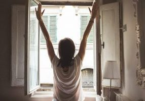Woman opening window starting the day positively